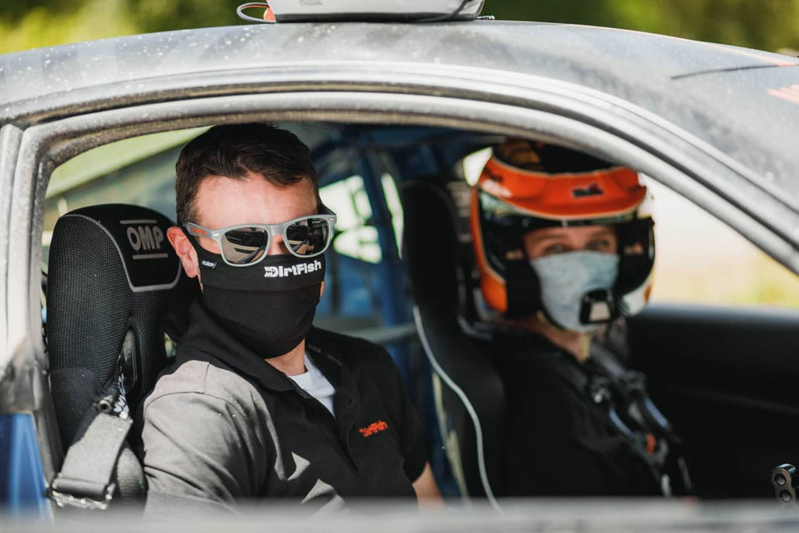 DirtFish Instructor and customer wearing a face mask in a rally car